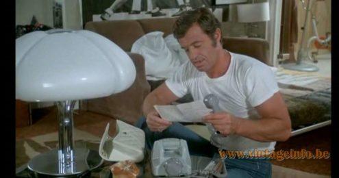Harrvey Guzzini Quadrifoglio table lamp in the film Le Corps De Mon Ennemi (1976)